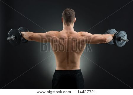 Rear View Of Strong Man Lifting Dumbbells