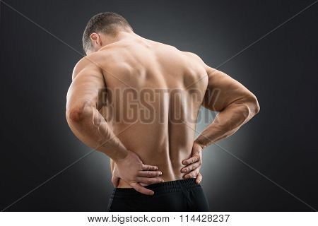 Rear View Of Muscular Man Suffering From Backache