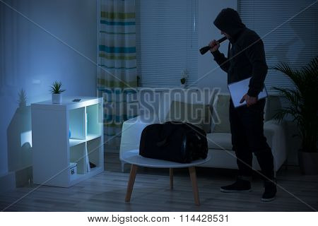 Thief Holding Flashlight At Shelves In Living Room