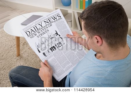 Man Reading News On Newspaper At Home