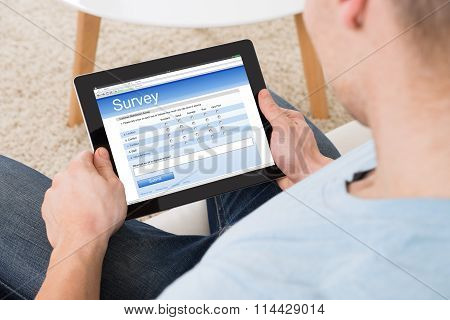 Man Filling Survey Form Online On Digital Tablet At Home