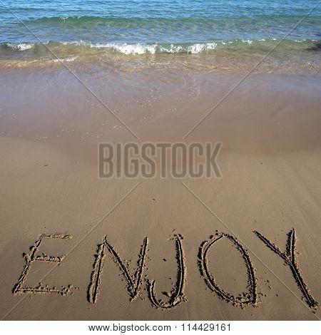 Word Enjoy Written On Sand