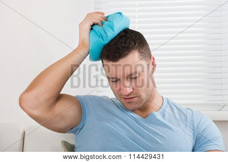 Upset Man Holding Hot Water Bottle On Head