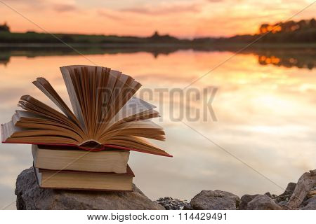 Stack of books and Open hardback book on blurred nature landscape backdrop against sunset sky with l