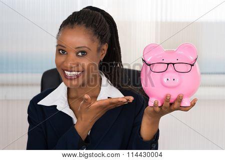 Smiling Businesswoman Holding Piggybank