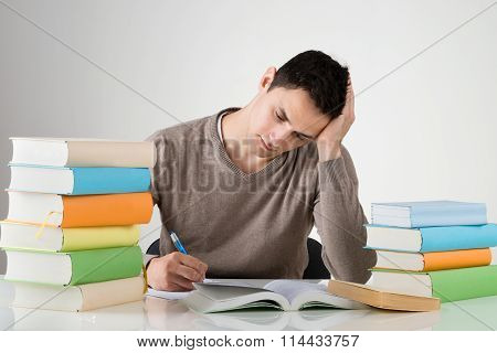 Exhausted Man Studying At Table