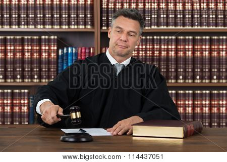 Confident Judge Striking The Gavel At Table