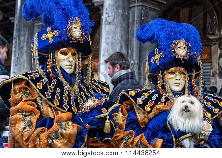 Couple with fantasy Carnival ??sk and a dog at Carnival of Venice