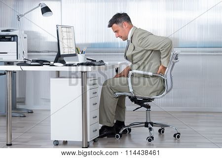 Accountant Suffering From Back Pain At Desk