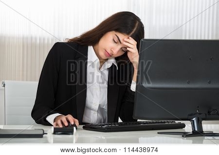 Businesswoman Sitting With Head In Hand At Computer Desk