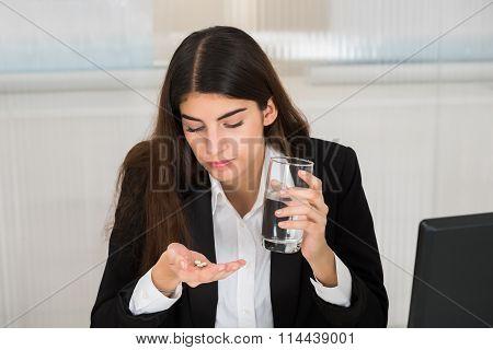 Businesswoman Taking Medicine In Office