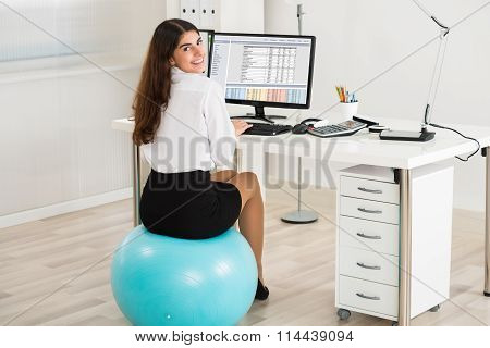 Businesswoman Using Computer While Sitting On Exercise Ball