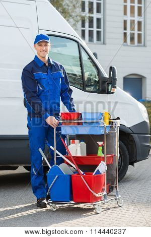 Happy Janitor Standing With Cleaning Equipment