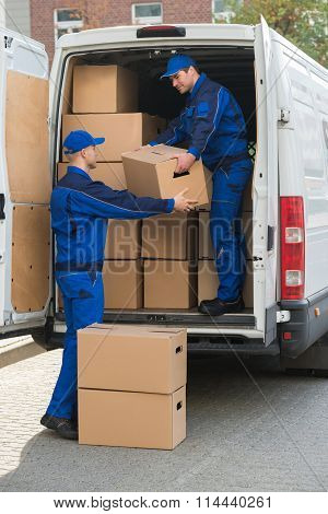 Delivery Men Unloading Cardboard Boxes From Truck