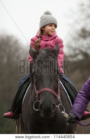 Little girl riding on a horse. Adult leading horse by bridle