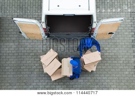 Delivery Men Unloading Cardboard Boxes From Truck On Street