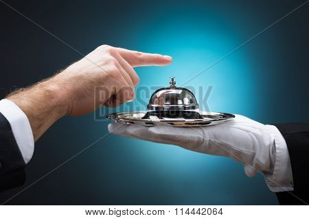 Businessman Ringing In Service Bell Held By Bellboy