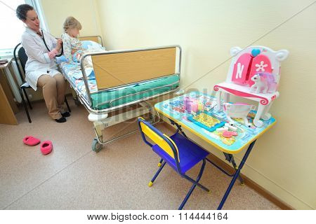 RUSSIA, MOSCOW - AUG 31, 2015: pediatric physician with stethoscope listening breath of young girl in multidisciplinary Clinic Center Endosurgery and Lithotripsy (CELT) (woman with model release)
