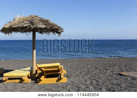 View Of Perissa Beach On The Greek Island Of Santorini With Sunbeds And Umbrellas. Beach Is Covered