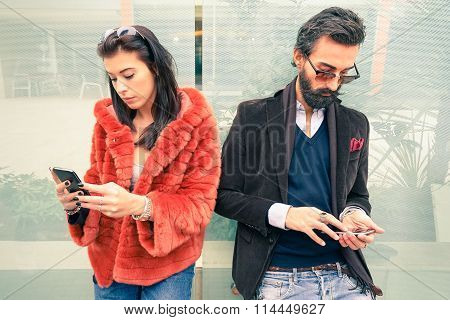 Hipster Couple In Sad Moment Ignoring Each Other Using Mobile Phones - Concept Of Apathy Sadness