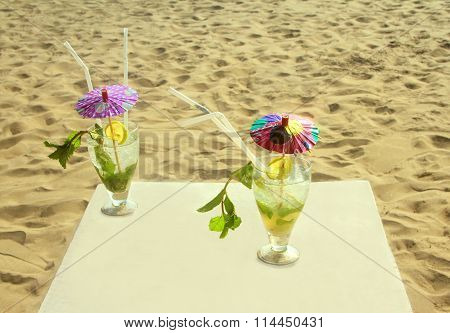 Mojito Cocktail With Ice, Rum, Lime And Mint In A Glass On Beach Sand