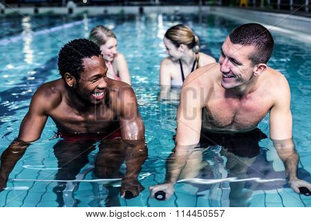 Fit smiling group pedaling on swimming bike in pool