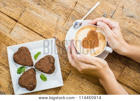 Woman Holding Hot Cup Of Coffee And Chocolate Cake In The Shape Of Heart