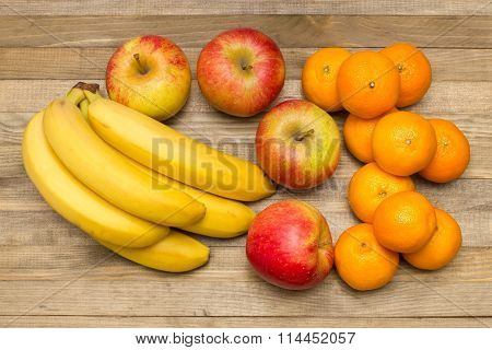 Group Of Apple Banana And Mandarin Fruits On Wood