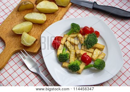 pieces of tofu served with broccoli, tomatoes and baked potatoes