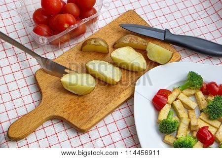 baked potatoes with tofu, broccoli and tomatoes served on checkered tablecloth