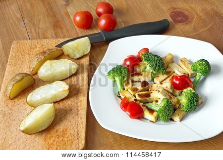 pieces of tofu with fresh vegetable and baked potatoes