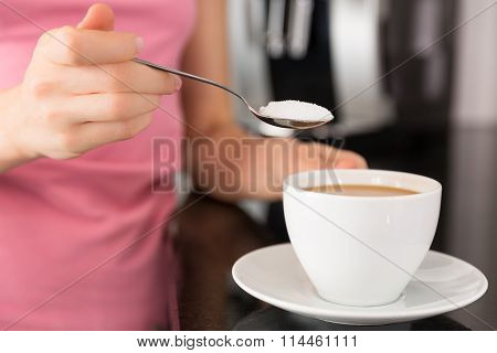 Woman Adding Sugar To The Coffee