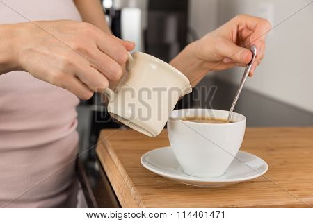 Woman Adding Milk To Her Coffee