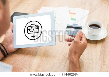 Photography apps against man holding credit card and digital tablet at table