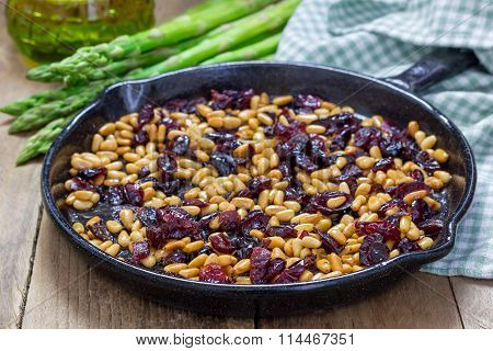 Roasted Pine Nuts With Dried Cranberries On A Cast Iron Skillet. Ingredients For An Appetizer With A