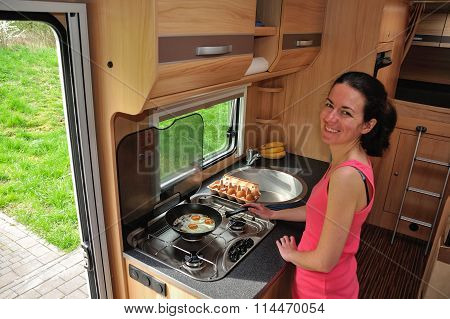 Family vacation, RV holiday trip, camping. Happy smiling woman cooking in camper. Motorhome interior
