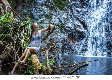 Young beautiful happy woman sitting near the waterfall.