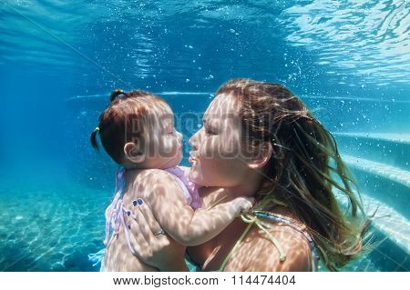 Mother With Child Swimming Underwater In Blue Beach Pool