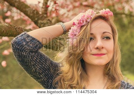 Portrait of a young woman with spring flowers. Toned image.