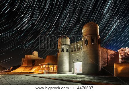 Western gate (Ata Darvoza) to ancient town of Itchan Kala at night with star trails. The city of Khiva, Uzbekistan