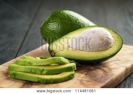 sliced ripe avocados on olive cutting board