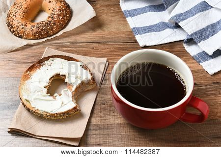 A fresh cup of coffee and a bagel with cream cheese on a wood table.