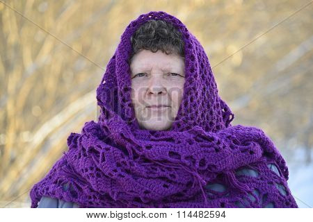 elderly woman in  purple  knitted shawl on her head