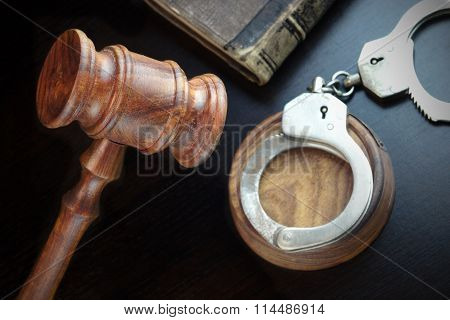 Judges Gavel, Handcuffs And Old Book On The Black Table