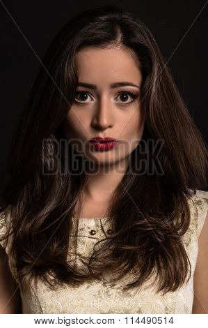 Lovely young brunette on a dark background.
