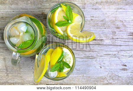 Lemonade. Water with lemon and mint in a glass on table