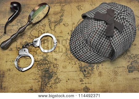 Overhead View Of  Deerstalker Hat And Private Detective Tools On The Old World Map Background. Items Include Vintage Magnifying Glass Smoking Pipe And Handcuffs