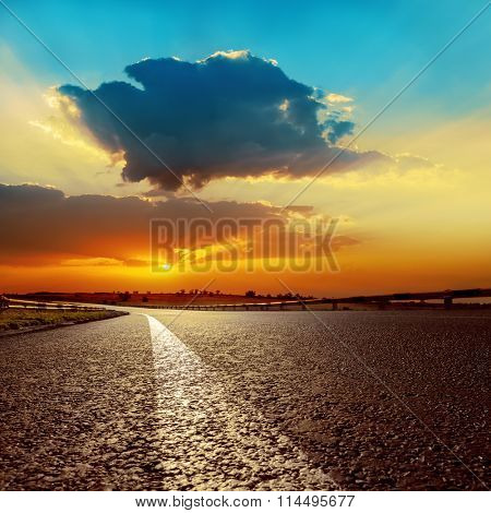 dramatic sunset over asphalt road closeup