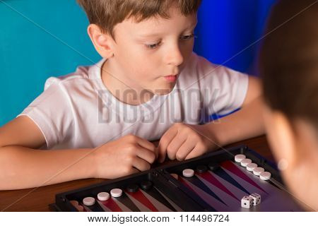 Boy Playing A Board Game Called Backgammon