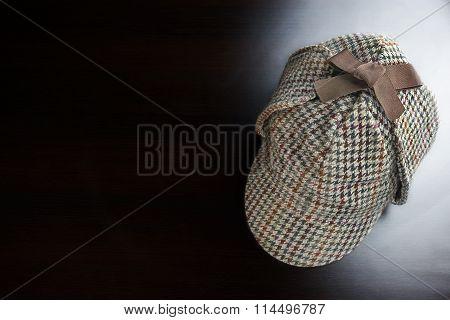 Sherlock  Deerstalker Hat On The Black Wooden Table